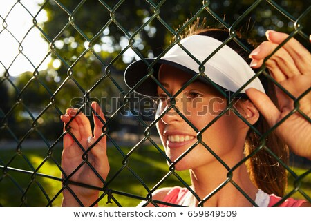 Woman peering through chain link fence Stock photo © IS2