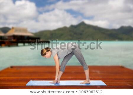 woman making yoga intense stretch pose outdoors Stock photo © dolgachov