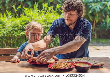 Father and son try Indian food in a cafe on the street Stock photo © galitskaya