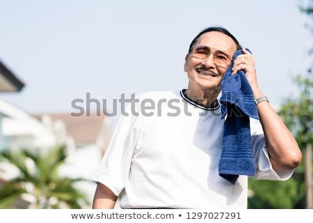 An elderly man wiping his sweat with napkin Stock photo © Kzenon