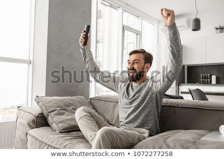 Portré derűs fiatalember tart távirányító irányítás Stock fotó © deandrobot