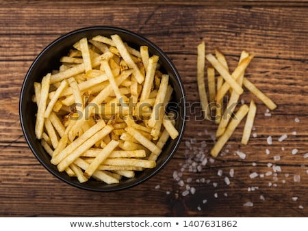 Salt and vinegar potato sticks in white bowl, classic snack on wooden background.  Stock photo © DenisMArt