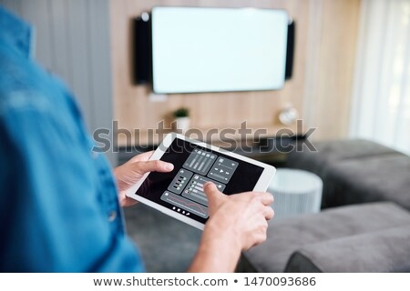 Stockfoto: Hands Of Young Man Holding Tablet With Smart Remote Control System
