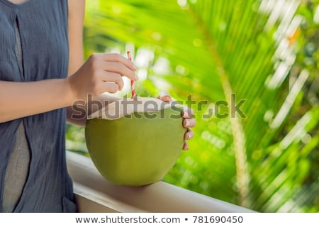 coconut in beautiful female hands on a green background. The Benefits of Coconut Water Concept Stock photo © galitskaya