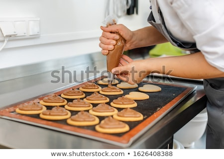 Confectioner woman using pastry bag to put cream on top of cookies Stock photo © Kzenon