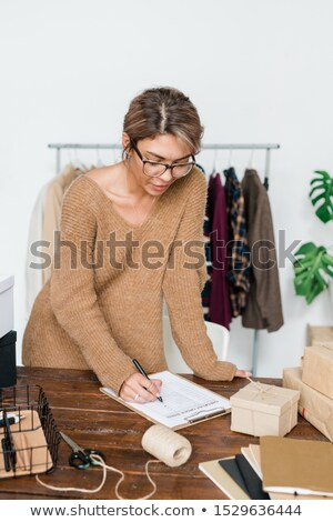 Young casual woman standing by wooden table and checking list of ordered items Stock photo © pressmaster