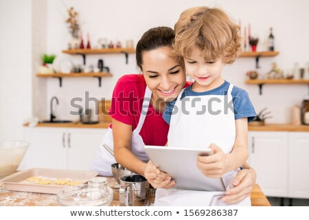 affectionate young woman and her son with touchpad watching video recipe stock photo © pressmaster