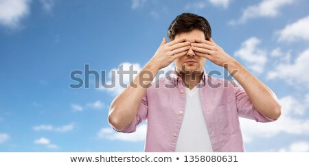 man closing his eyes by hands over blue sky Stock photo © dolgachov