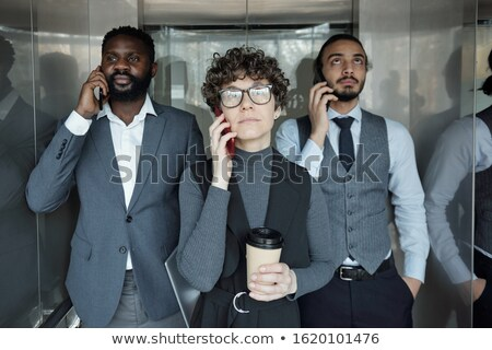 Young intercultural business people calling by smartphones in elevator Stock photo © pressmaster