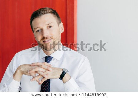 Photo of handsome intelligent man with gentle smile, keeps hands together, wears formal white shirt, Stock photo © vkstudio