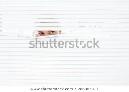 a blonde woman looks through blinds Stock photo © photography33