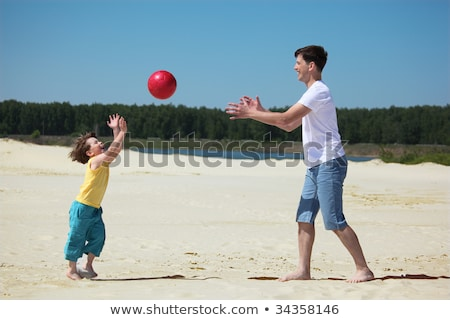 son throws ball to father on sand stock photo © paha_l