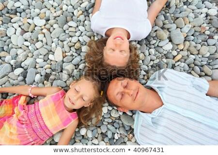 Stock photo: Happy family with little girl lying on stony beach, closed eyes,