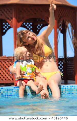 two beautiful women sitting on ledge pool open-air Stock photo © Paha_L