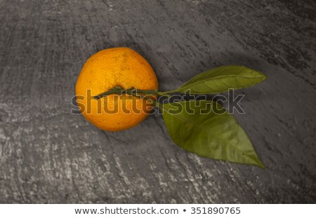 Fresh juicy tasty Sicilian tangerines with a foliage branch on a stone background. Stock photo © mcherevan