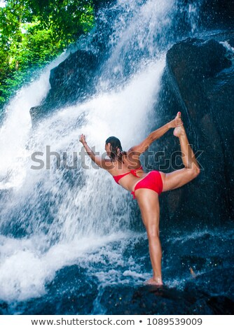 Young woman doing yoga exercise under waterfall Stock photo © konradbak