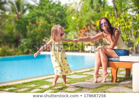happy women relaxing and having fun together near swimming pool stock photo © deandrobot
