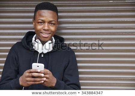 Teenage Boy Wearing Headphones And Listening To Music In Urban  Stock photo © Yatsenko