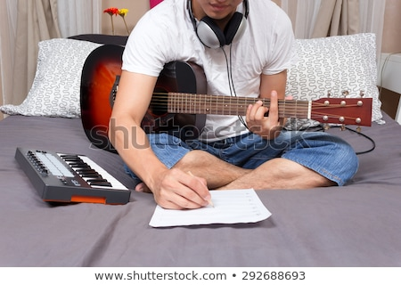 man playing guitar on bed stock photo © is2