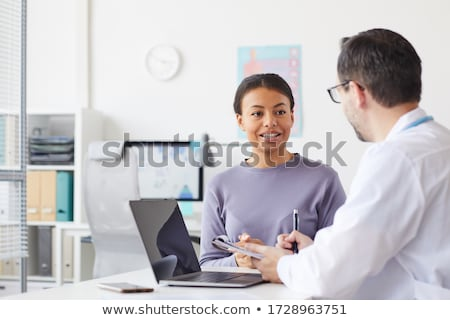 man sitting opposite woman in office stock photo © is2