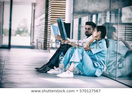 Stressed doctor and nurse sitting on floor examining X-ray report Stock photo © wavebreak_media