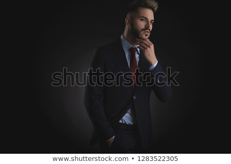 portrait of smiling pensive businessman in navy suit standing Stock photo © feedough