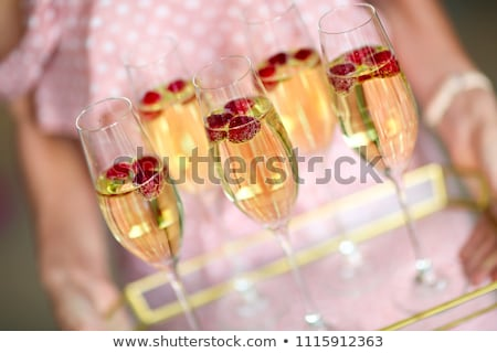 Stock photo: Young woman with champagne glasses on tray