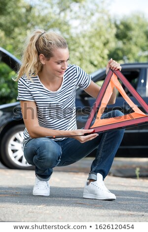 Pretty, young woman setting the safety triangle on the roadside  Stock photo © lightpoet