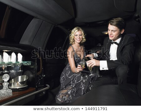 Women and men celebrating with drinks in a limousine car Stock photo © Kzenon