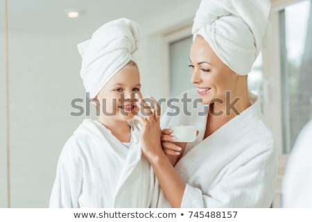 cute smiling mother and daughter applying face cream stock photo © dashapetrenko