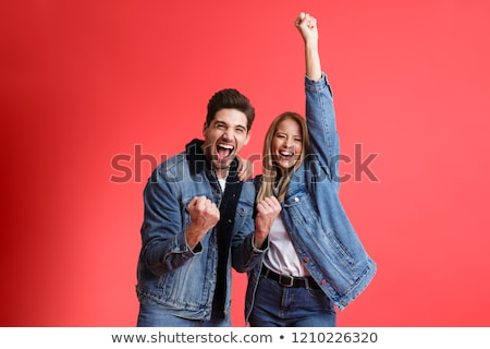 portrait of a cheerful young man dressed in denim jacket stock photo © deandrobot