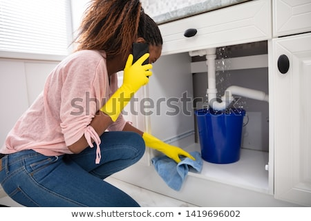 woman placing bucket under water leaking from sink pipe stock photo © andreypopov