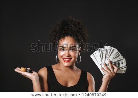 happy african woman posing isolated over black wall holding money and chips stock photo © deandrobot