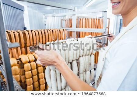 Butcher woman showing sausages on a rail ストックフォト © Kzenon