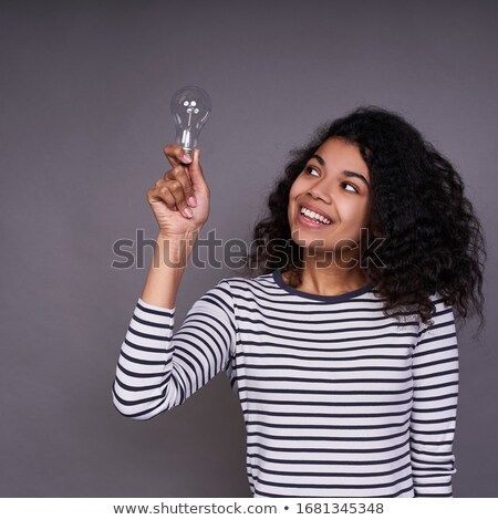 young woman holding light bulb in her mouth stock photo © konradbak