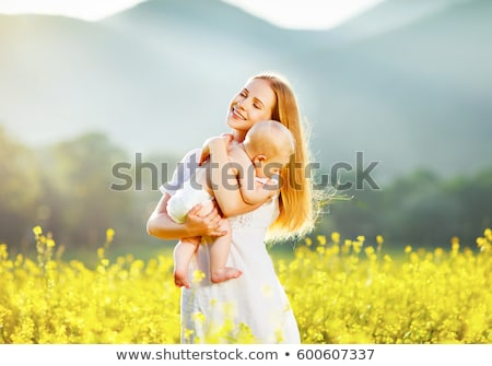 happy family mother and child daughter embrace on yellow flowers on nature in summer stock photo © lopolo