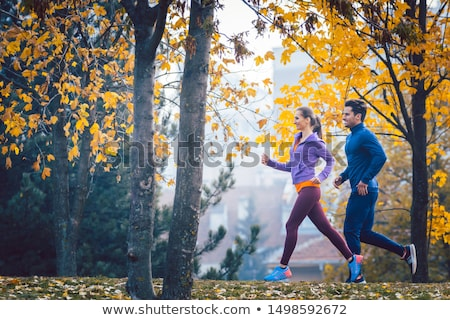 Woman and man jogging or running in park during autumn Stock photo © Kzenon
