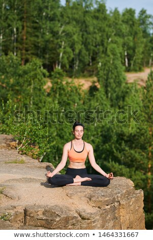 Peaceful young woman with closed eyes sitting with crossed legs in mountains Stock photo © pressmaster