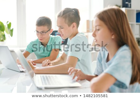 three young schoolkids in casualwear sitting in computer classroom stock photo © pressmaster