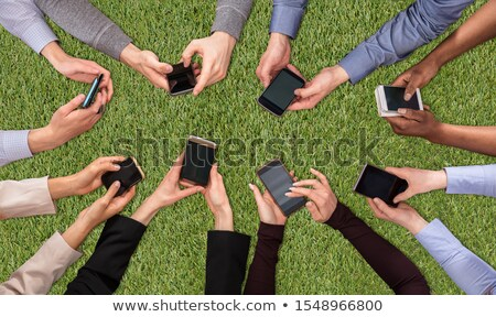 hands social networking with mobile cellphones on green turf stock photo © andreypopov