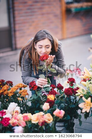 Woman standing outside a florist choosing flowers Stock photo © lovleah