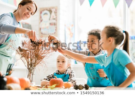 Teacher and schoolkids in aprons putting handmade paper bats on dry branches Stock photo © pressmaster