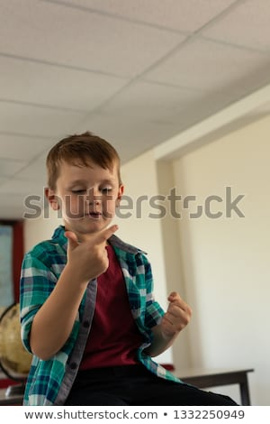 Front view of Caucasian boy counting with his finger at desk in a classroom at elementary school Stock photo © wavebreak_media