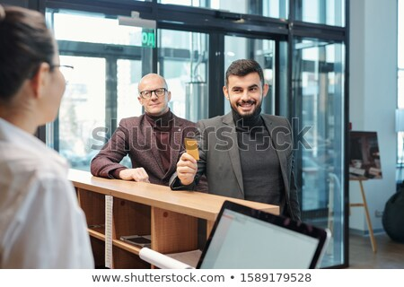 One of contemporary business travelers showing plastic card to receptionist Stock photo © pressmaster