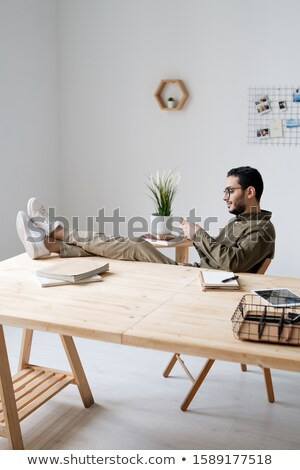 Young business employee in casualwear scrolling in smartphone by workplace Stock photo © pressmaster