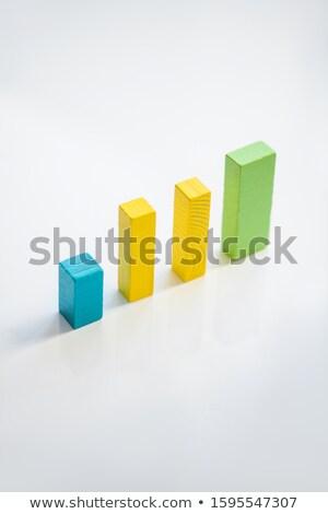 Row of blue, yellow and green flat wooden bricks making up financial chart Stock photo © pressmaster