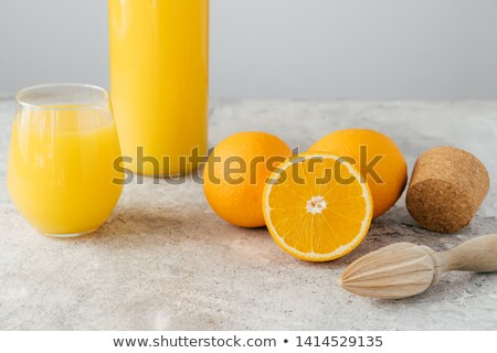 Freshly made orange juice containing vitamin C, sliced oranges, wooden cork and squeezer. Process of Stock photo © vkstudio