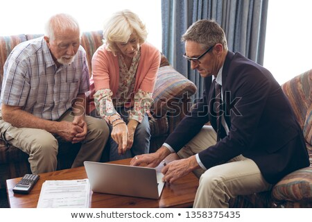 Front view of matured Caucasian male physician and senior Caucasian couple discussing over laptop at Stock photo © wavebreak_media