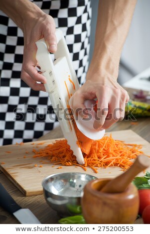 cutting carrot with stainless grater stock photo © vladacanon
