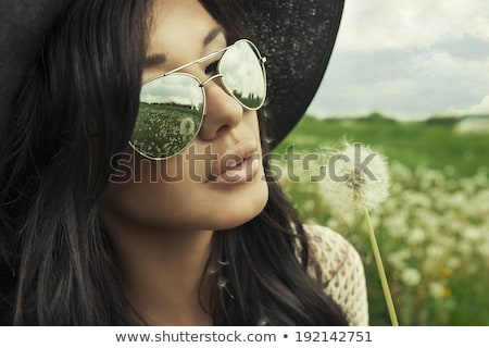beautiful girl blows on dandelion in white hat stock photo © ruslanomega